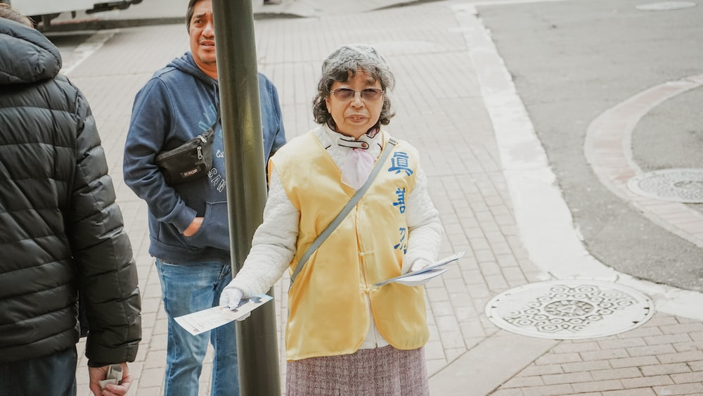 woman in yellow jacket and blue denim jeans standing beside gray metal post