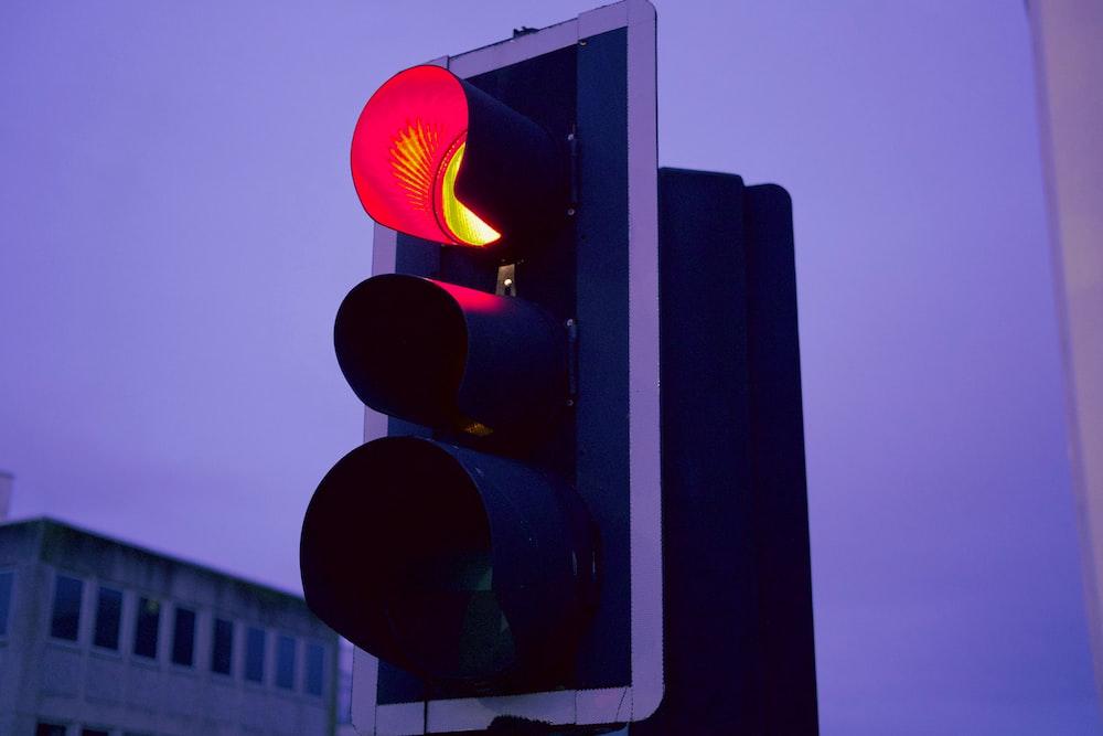black traffic light turned on during daytime