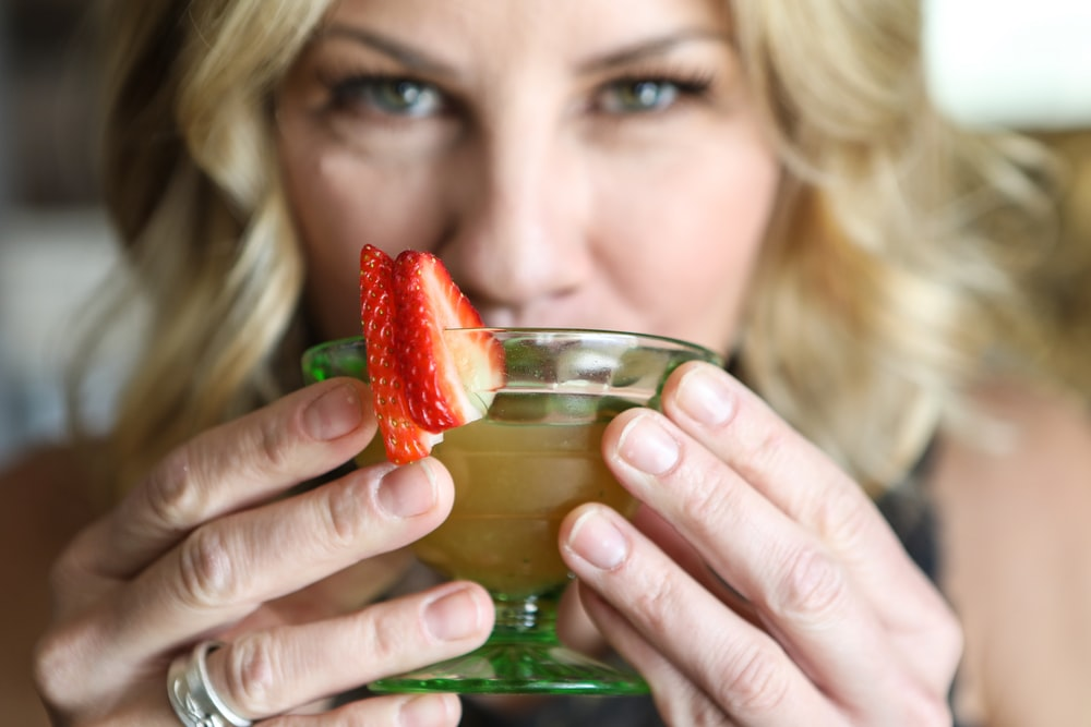 woman holding clear glass cup with strawberry juice