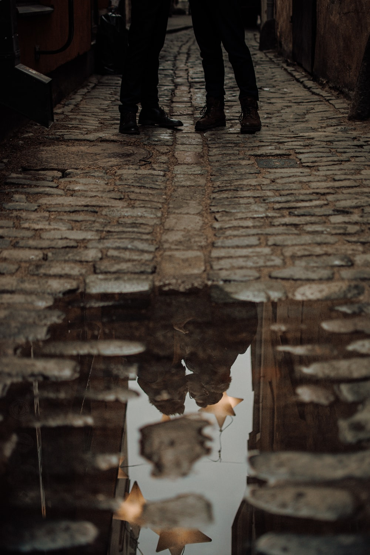 person in black pants walking on brown brick floor