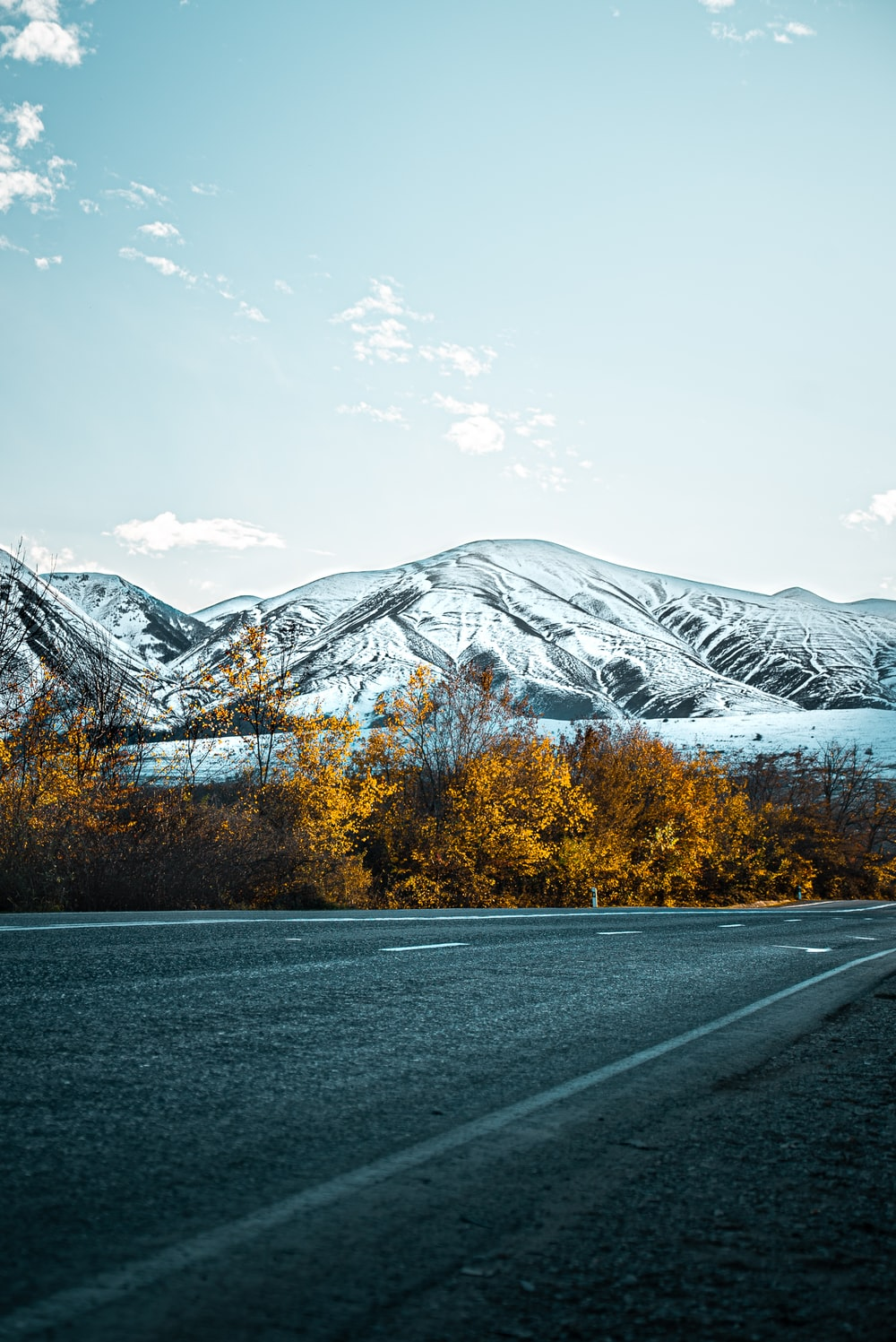 gray asphalt road near snow covered mountain during daytime