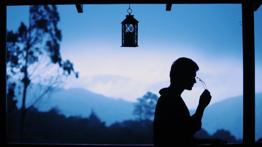 silhouette of man standing near lantern during daytime