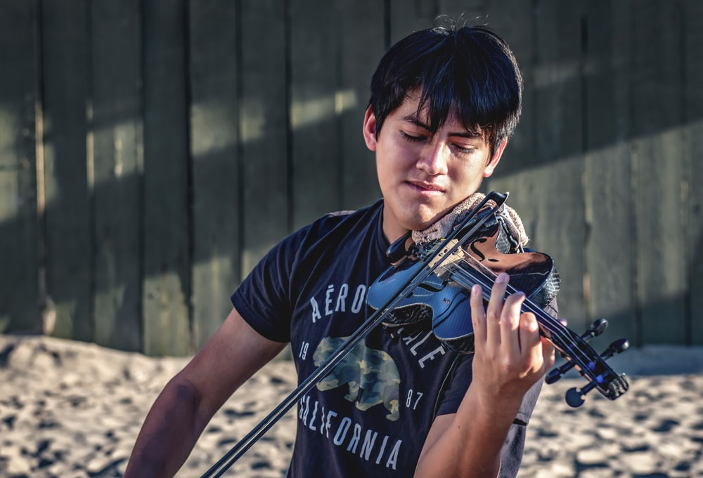 man in blue and white crew neck t-shirt playing violin