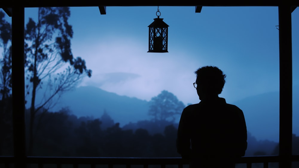 silhouette of man standing near mountain during daytime