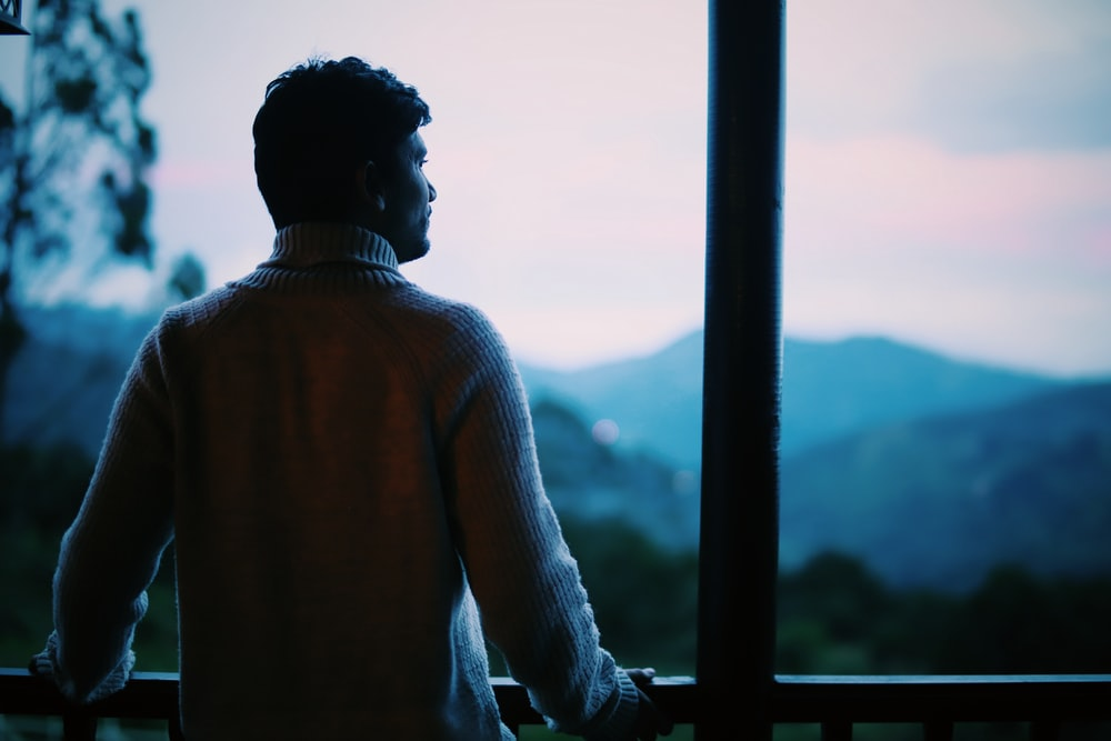 man in brown sweater looking at the city during daytime