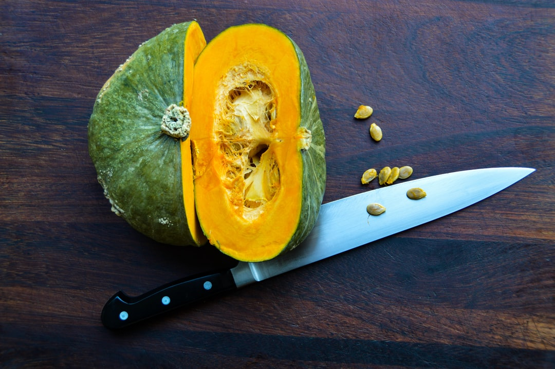 Sliced green and orange squash makes a high contrast highlight on a dark wood board