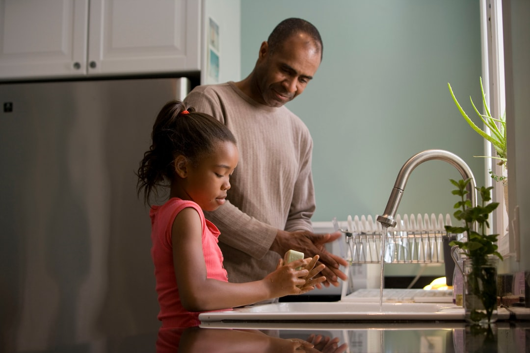 This African-American father was shown in the process of teaching his young daughter how to properly wash her hands at their kitchen sink, briskly rubbing her soapy hands together under fresh running tap water, in order to remove germs, and contaminants, thereby, reducing the spread of pathogens, and the ingestion of environmental chemicals or toxins. Children are taught to recite the Happy Birthday song, during hand washing, allotting enough time to completely clean their hands.
