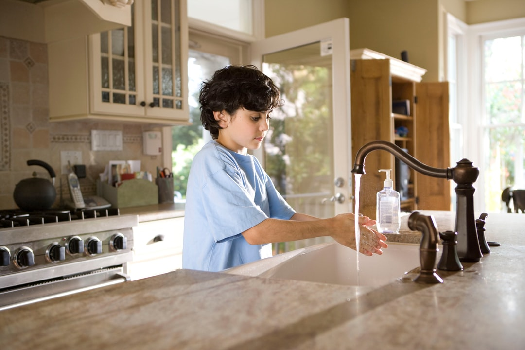This young boy was shown in the process of properly washing his hands at his kitchen sink, briskly rubbing his soapy hands together under fresh running tap water, in order to remove germs, and contaminants, thereby, reducing the spread of pathogens, and his ingestion of environmental chemicals or toxins. Children are taught to recite the Happy Birthday song, during hand washing, allotting enough time to completely clean their hands.