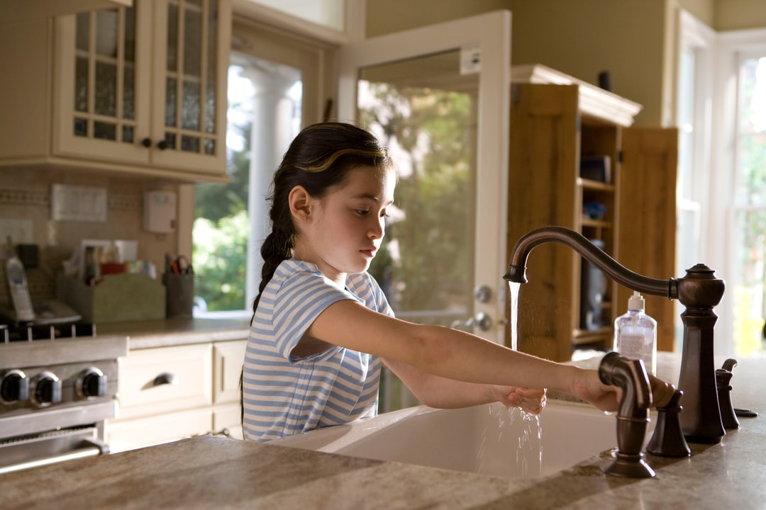 This young girl was shown in the process of properly washing her hands at her kitchen sink, briskly rubbing her soapy hands together under fresh running tap water, in order to remove germs, and contaminants, thereby, reducing the spread of pathogens, and her ingestion of environmental chemicals or toxins. Children are taught to recite the Happy Birthday song, during hand washing, allotting enough time to completely clean their hands.