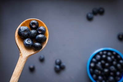 black berries on brown wooden spoon blueberry zoom background