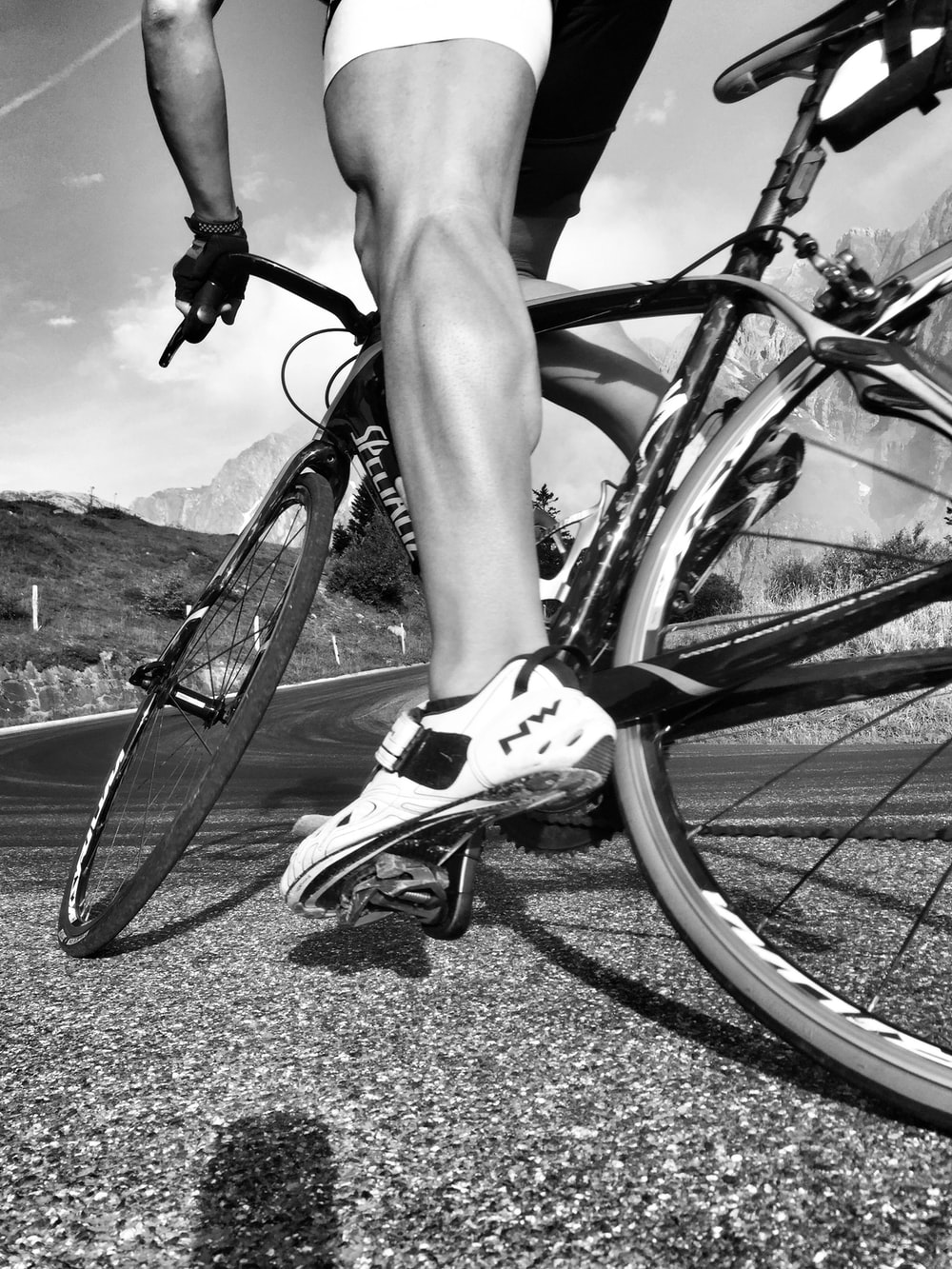 grayscale photo of person riding on bicycle