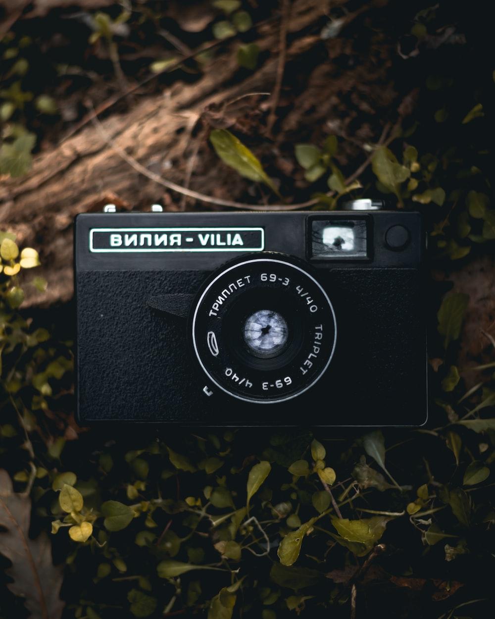 black and silver nikon camera on green grass