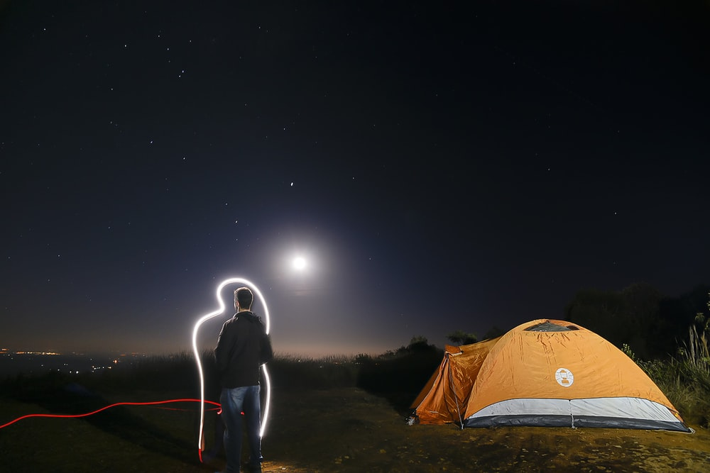 man in black jacket standing near orange dome tent during night time