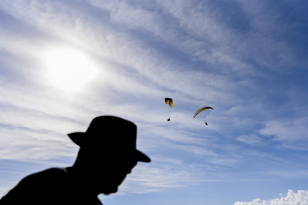 silhouette of person with parachute in mid air during daytime