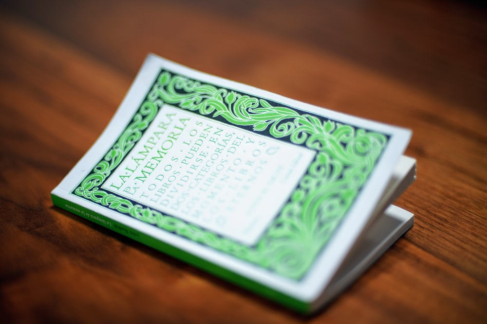 white and green book page on brown wooden table
