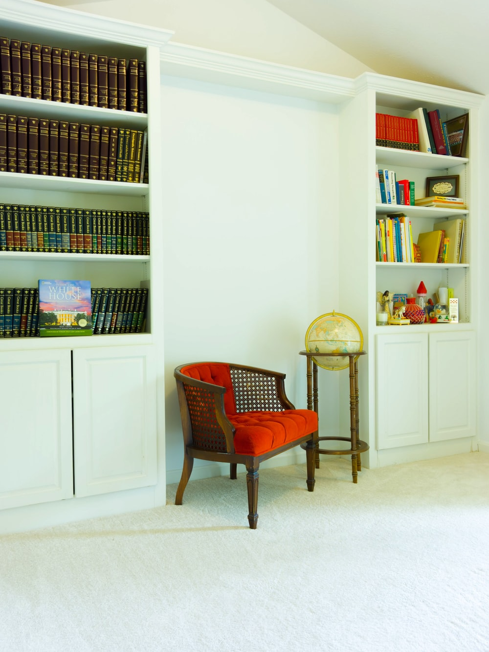 red padded brown wooden armchair beside white wooden shelf