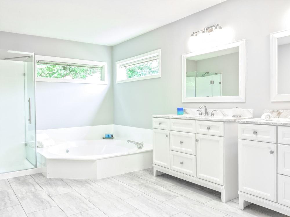 white ceramic bathtub near white wooden vanity sink