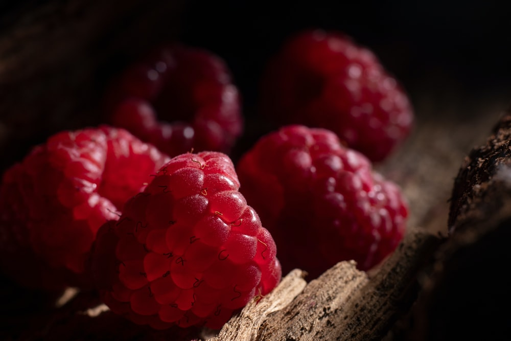 red raspberries on brown wooden surface