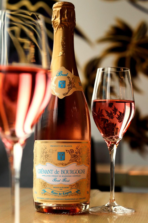 brown glass bottle beside clear wine glass