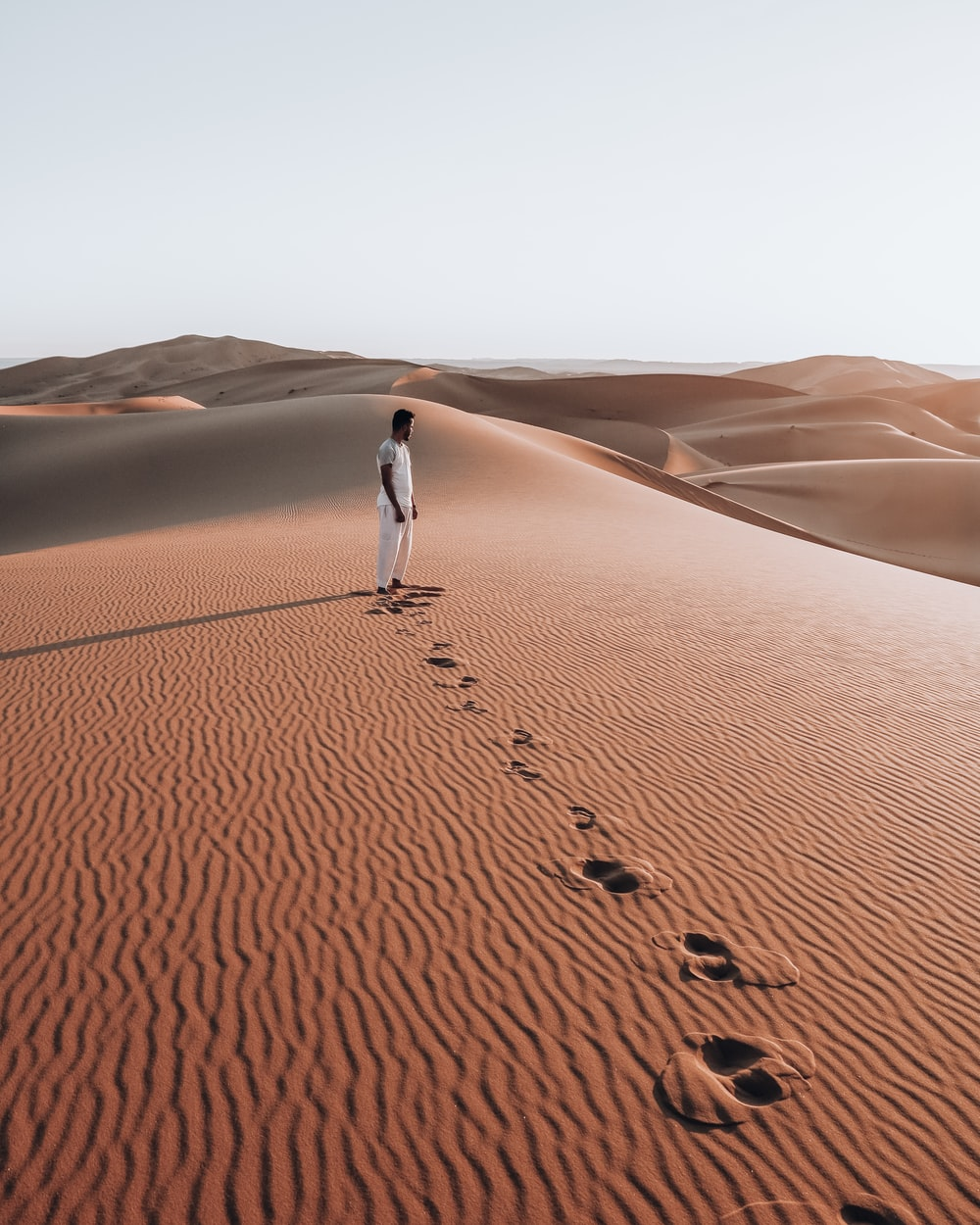 person in white shirt walking on desert during daytime