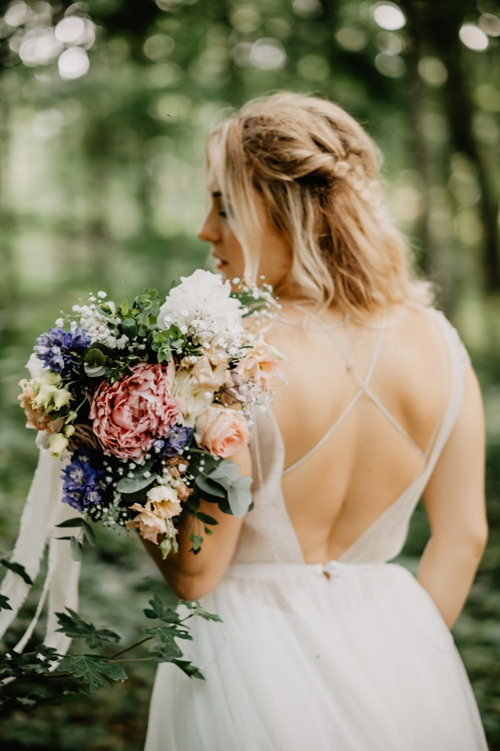 woman in white tube dress holding bouquet of flowers