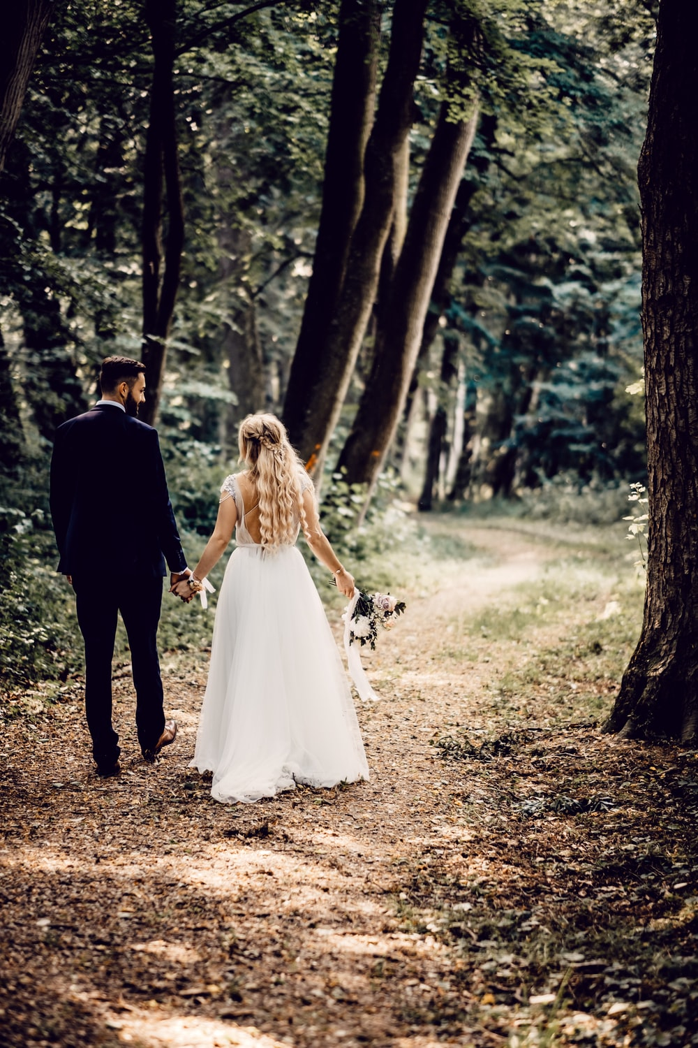 man and woman walking on forest during daytime