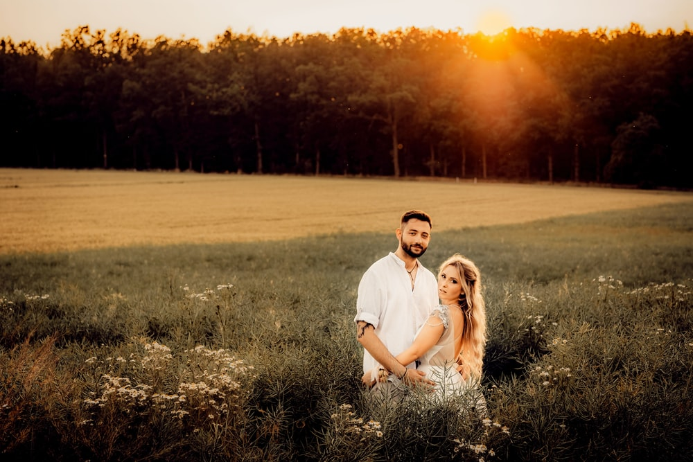 man in white polo shirt hugging woman in white dress on green grass field during sunset