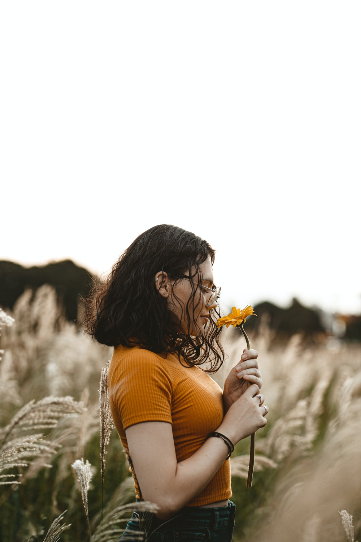 woman in orange tank top holding yellow flower during daytime