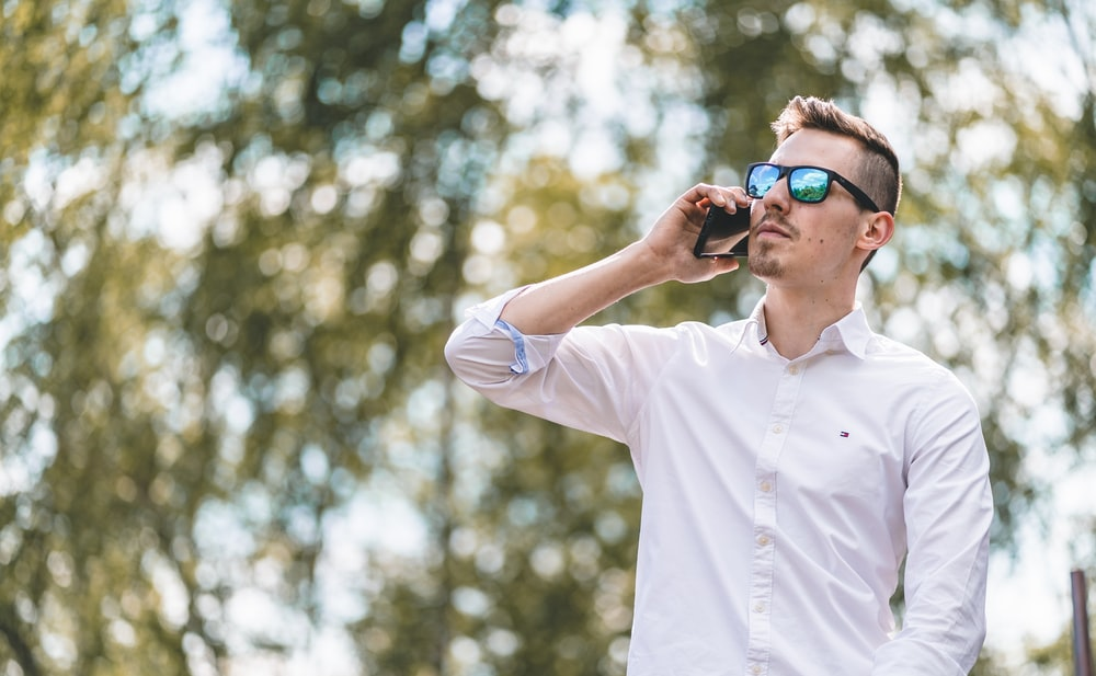 man in white polo shirt wearing blue sunglasses