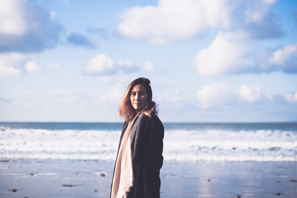woman in black coat standing on beach during daytime