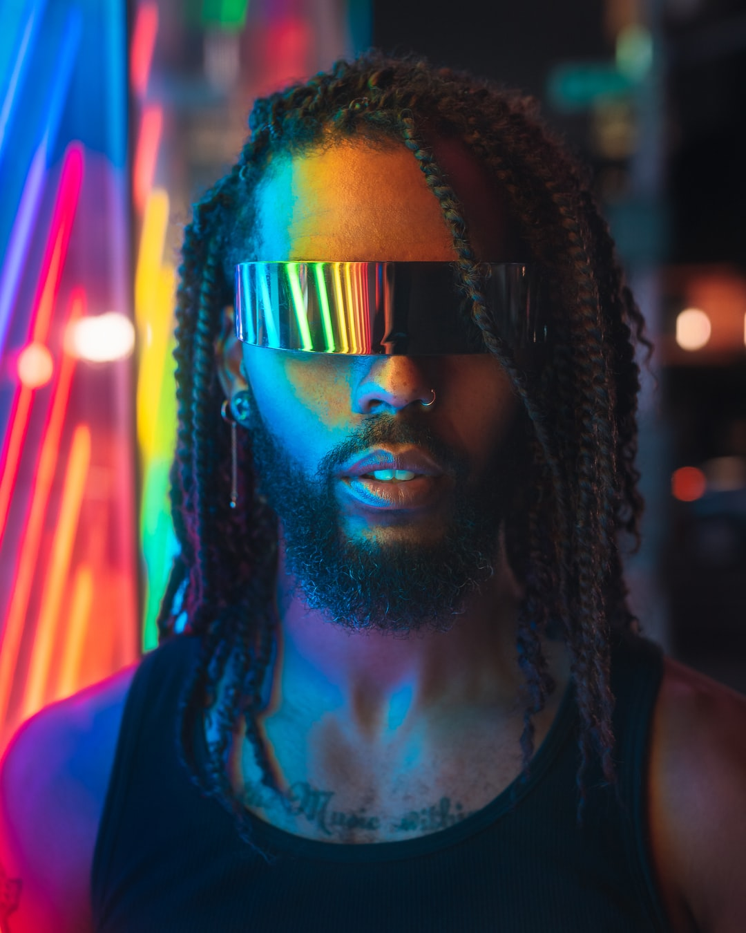 An image of a dark-skinned, dreadlocked man with a mirrored visor standing before a colorful wall of blurred neon light.