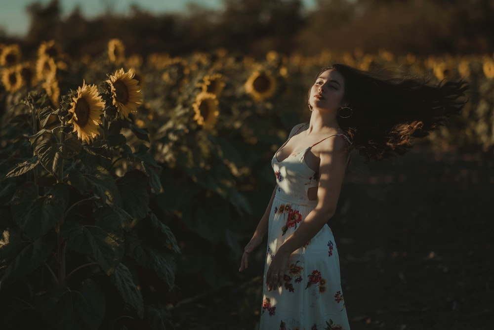 woman in white and red floral dress standing on sunflower field during daytime