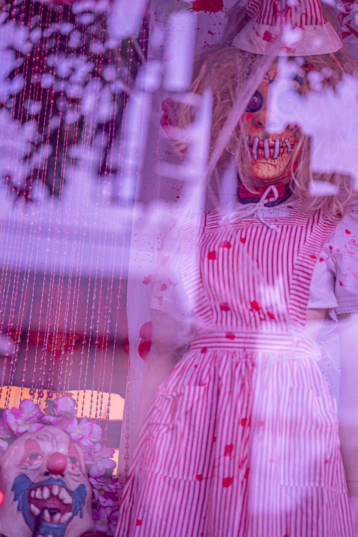 woman in pink dress standing beside window