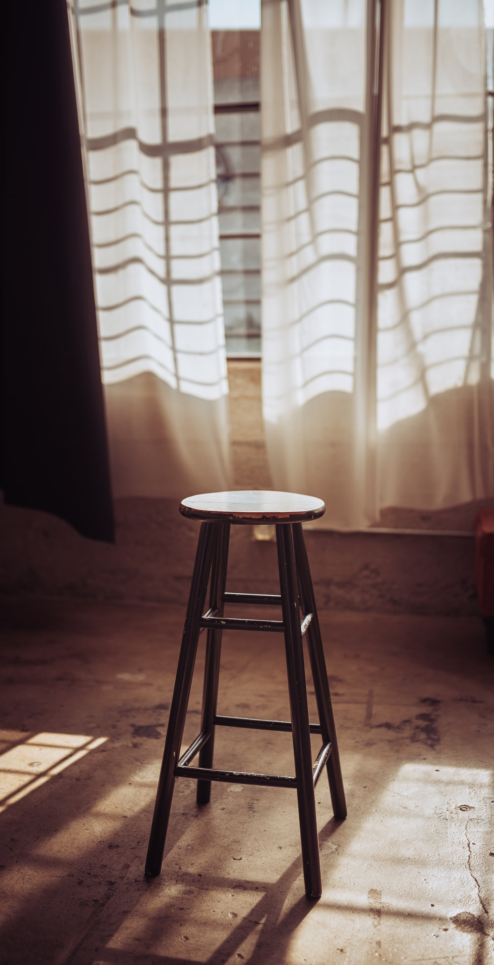 brown wooden stool near white curtain