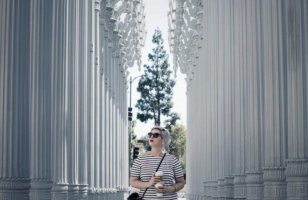 woman in black and white stripe shirt standing near white curtain