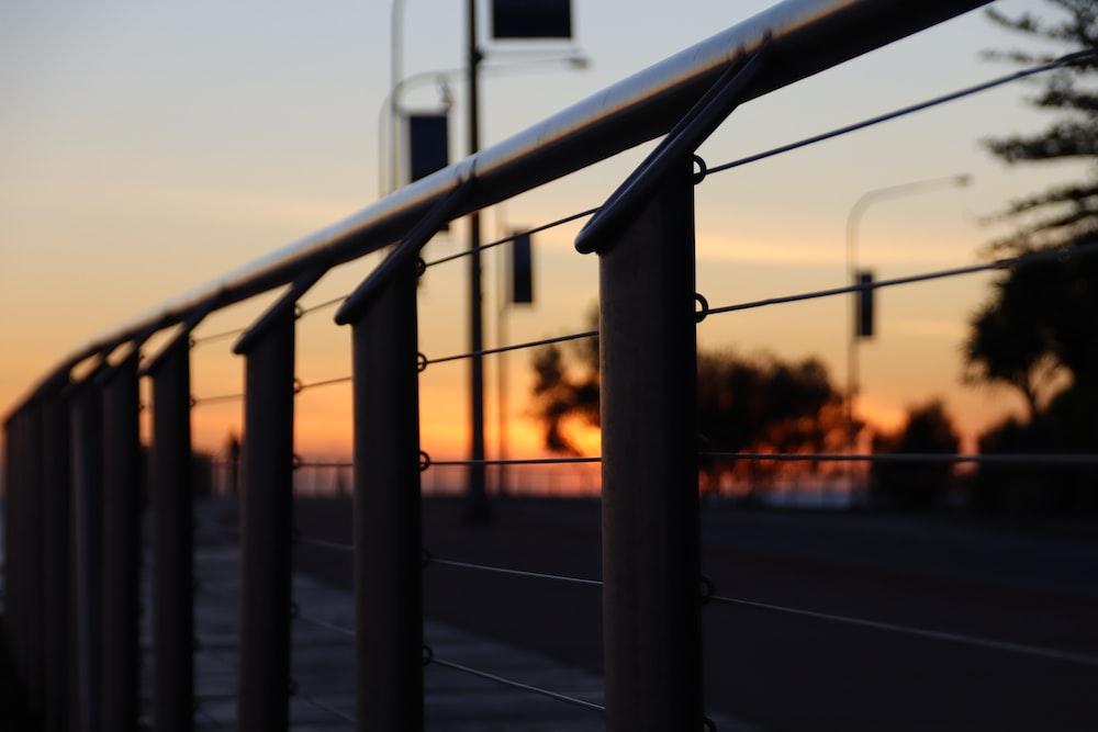 black metal railings during sunset