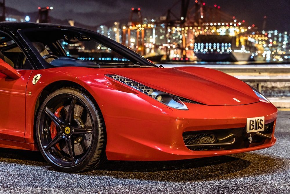 red ferrari 458 italia parked near white and brown building during night time