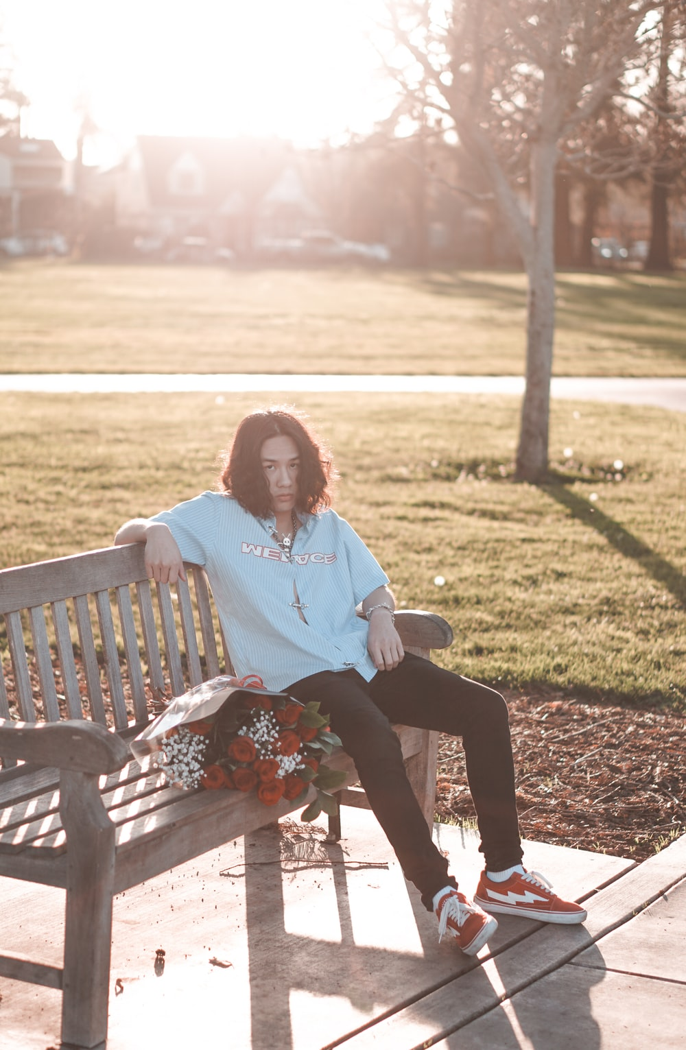 woman in white long sleeve shirt sitting on brown wooden bench during daytime