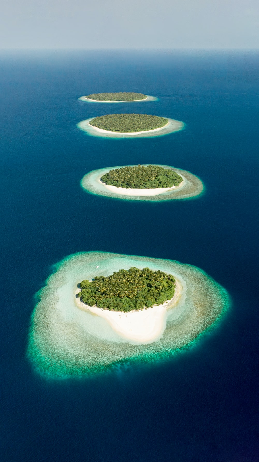 green and brown island in the middle of blue water