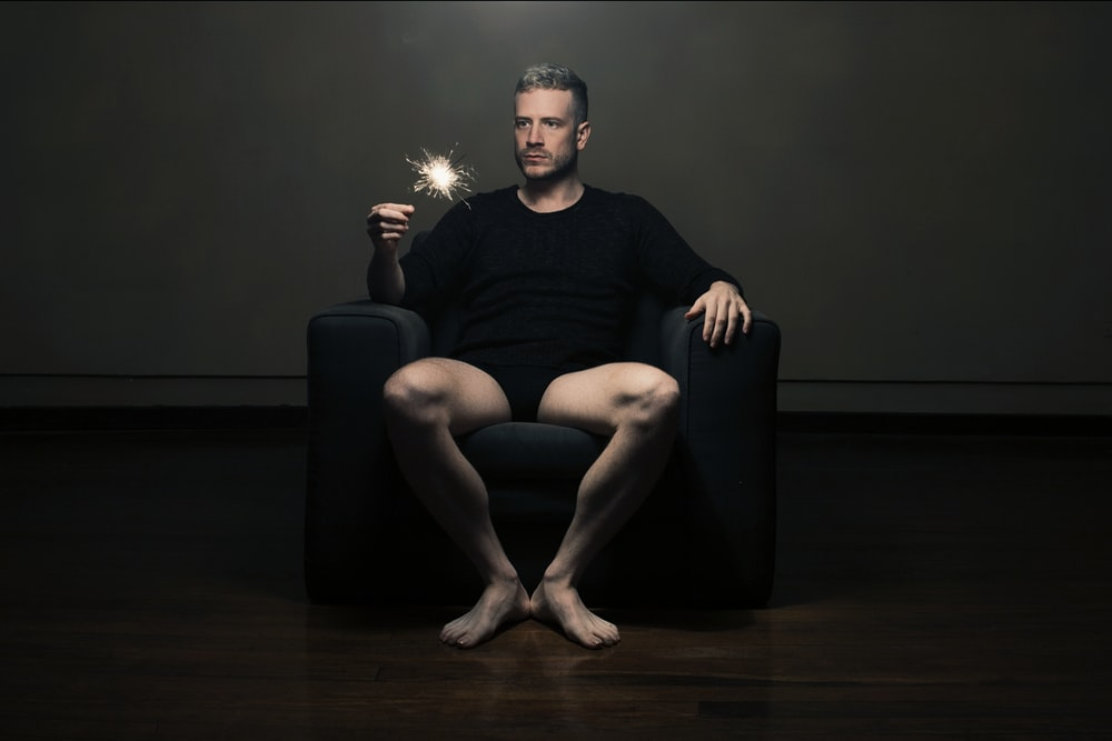 man in black tank top sitting on black leather armchair