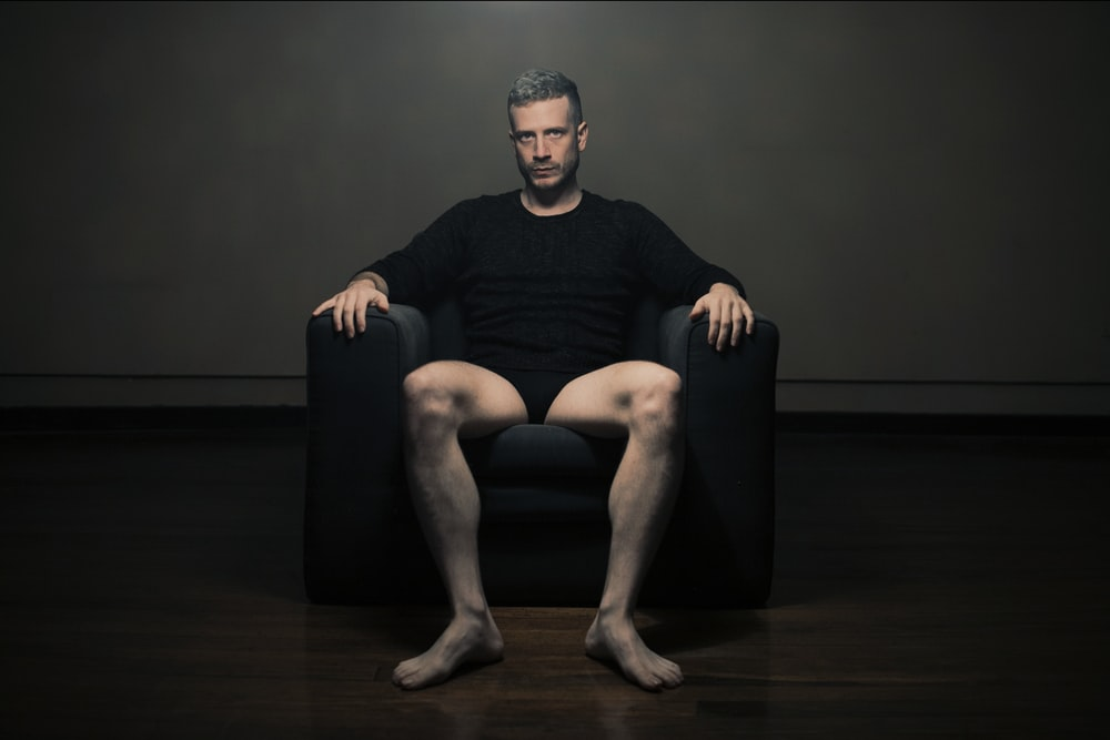 man in black crew neck t-shirt sitting on black leather armchair