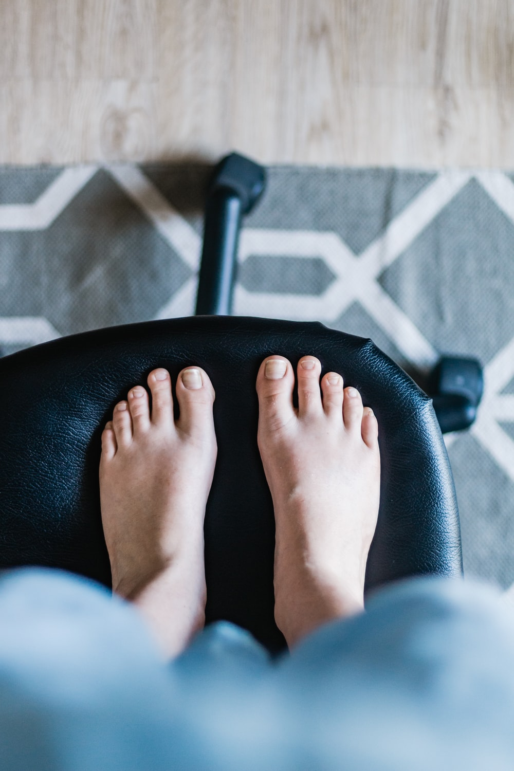 persons feet on black leather chair