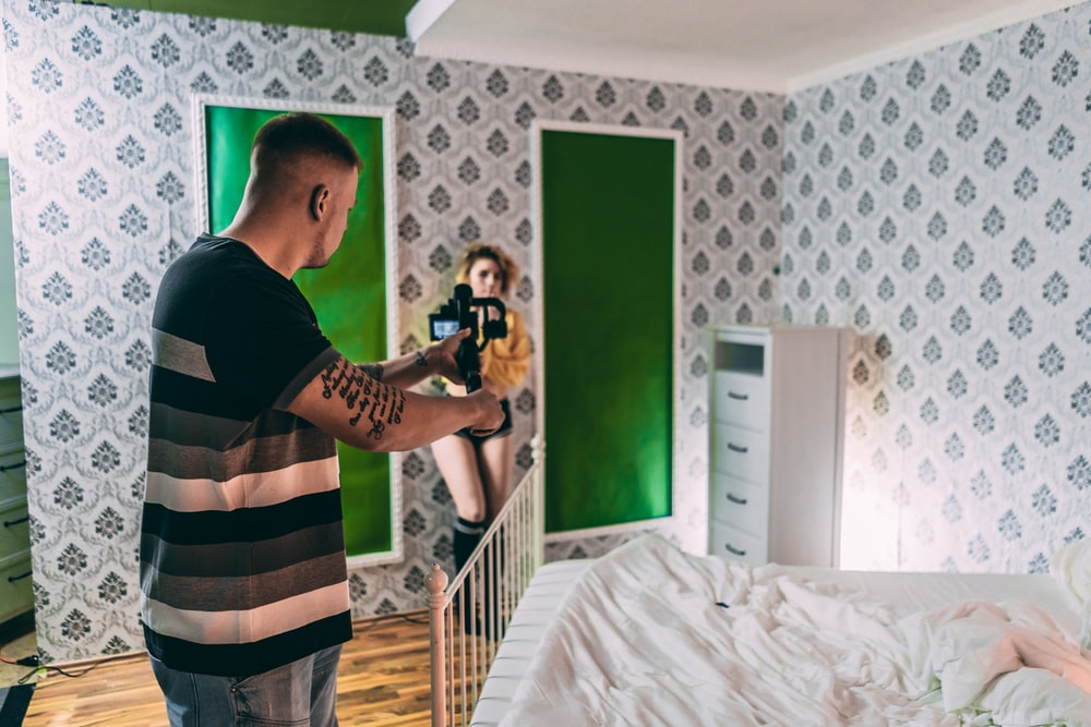 man in black t-shirt and plaid shorts standing beside bed