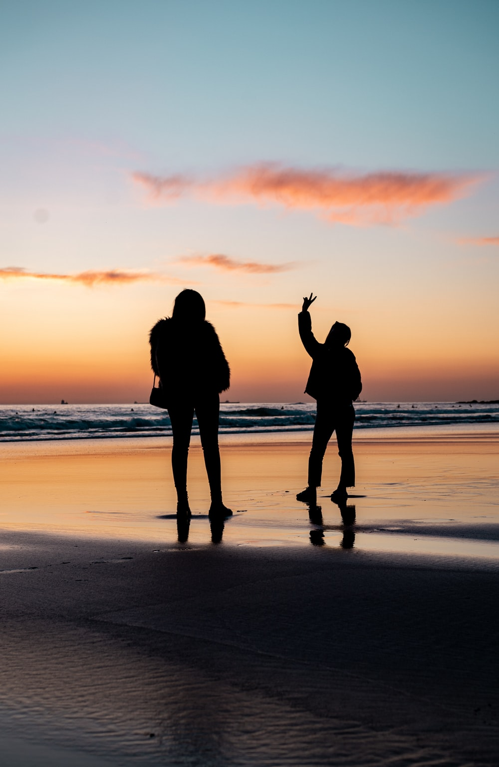 silhouette of 2 person standing on beach during sunset