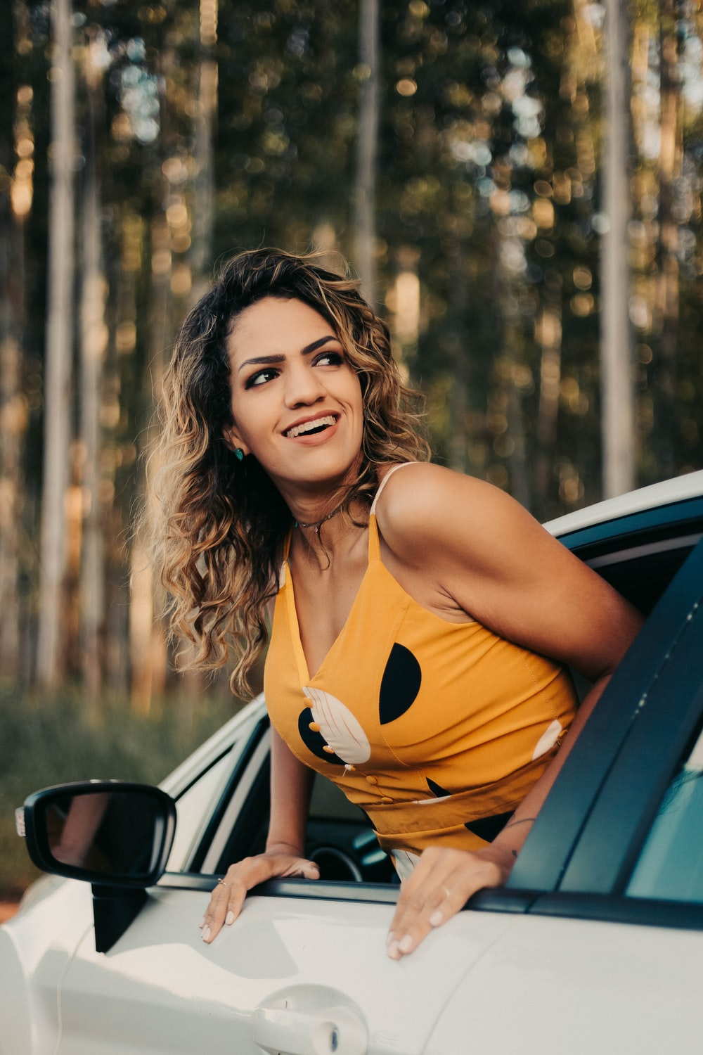 woman in orange tank top sitting on car