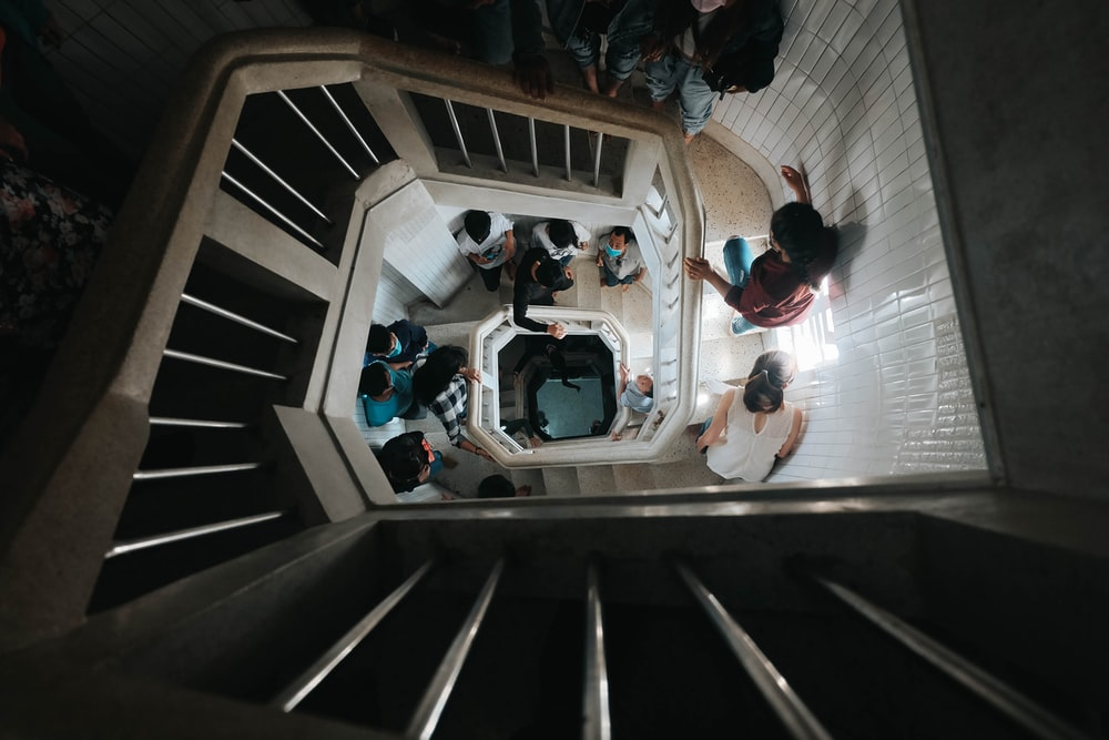 people in white and blue shirts sitting on stairs
