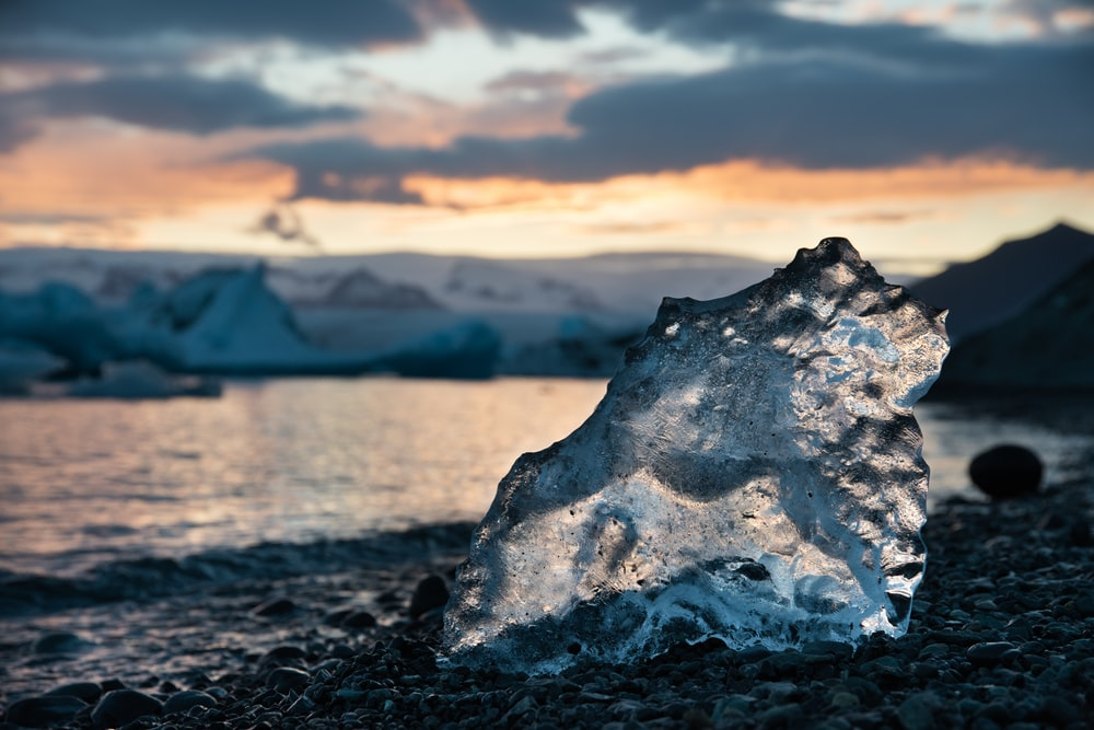 ice on black rocky shore during daytime