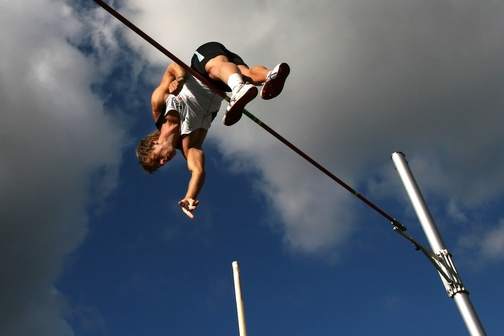 man in white tank top and black shorts hanging on black metal bar under blue sky