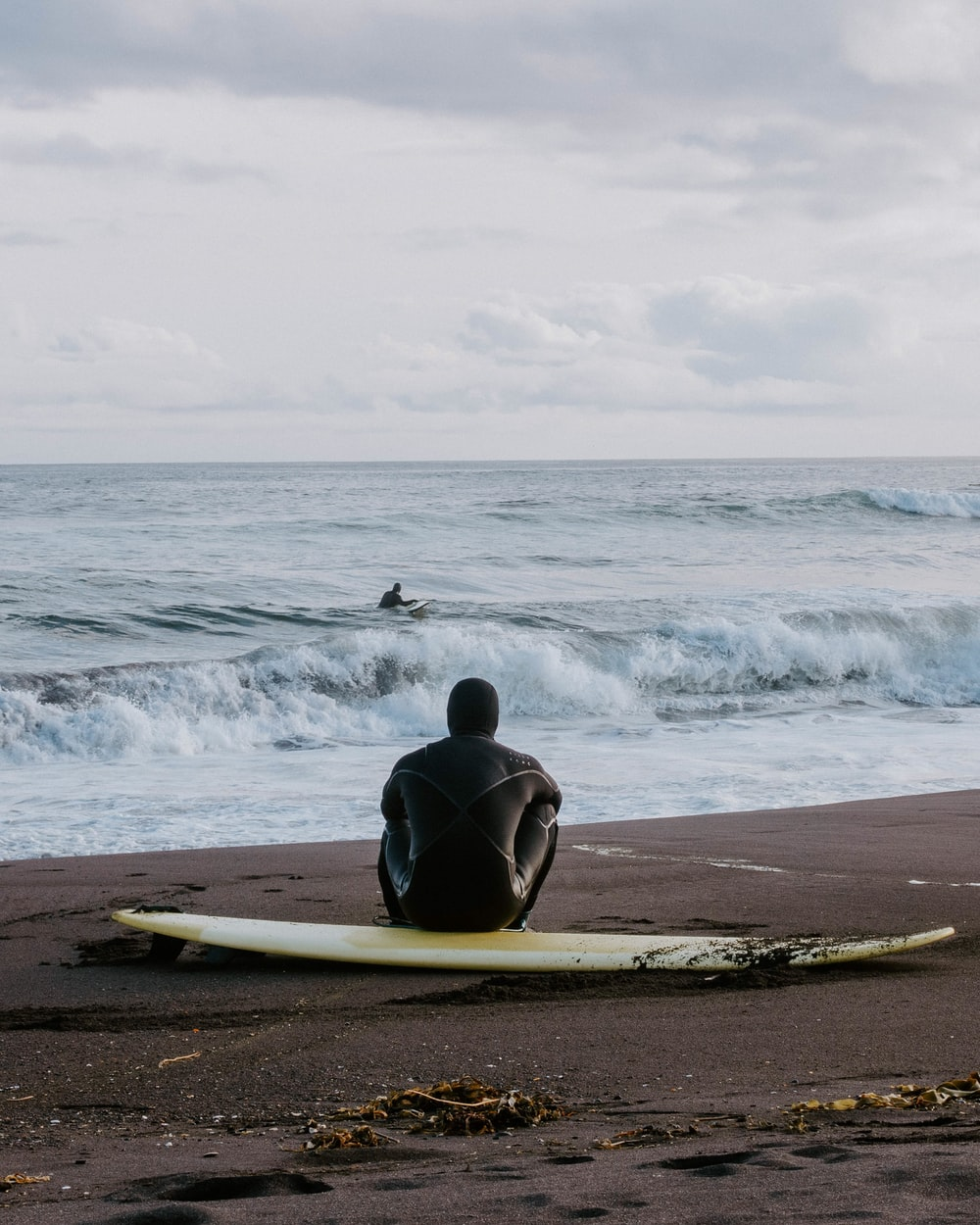 man in black wet suit sitting on white surfboard on beach during daytime