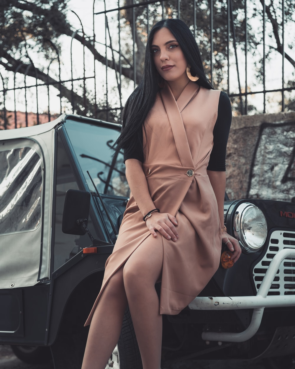 woman in brown long sleeve dress standing beside white car during daytime